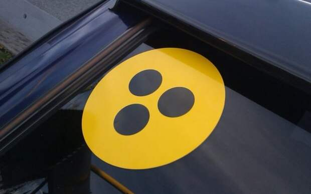 Что означает знак желтого круга с черными точками на стекле авто