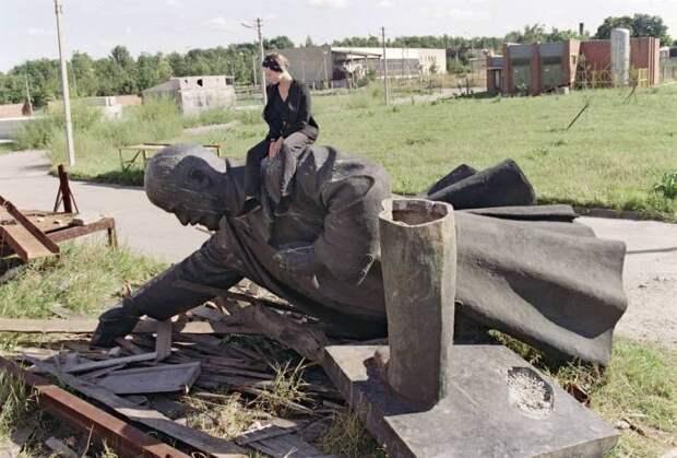 Молодая девушка сидит на сброшенной статуе Ленина в Вильнюсе.