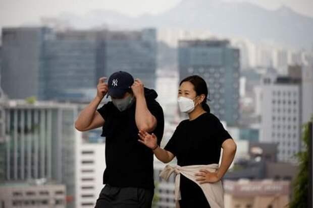 A couple wearing masks to avoid contracting the coronavirus disease (COVID-19) take a walk at a park in Seoul, South Korea, May 26, 2021. REUTERS/Kim Hong-Ji