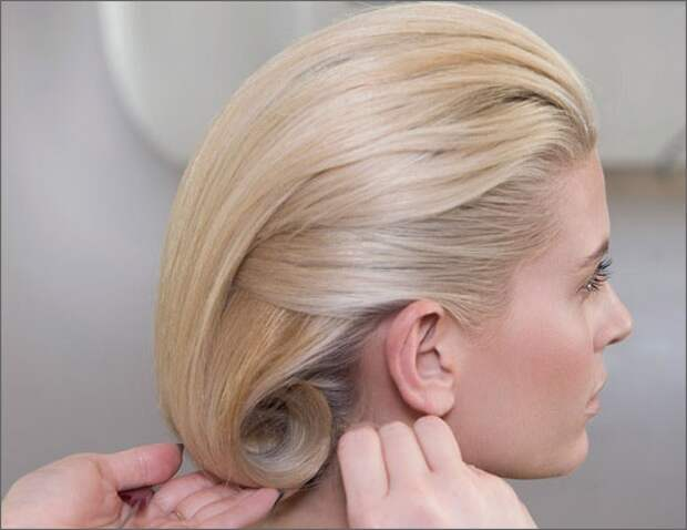 Верхнюю часть волос слегка начёсываем, зачёсываем вниз, заворачиваем концы в валик (можно воспользоваться круглой плойкой или подложить валик) и закрепляем невидимками (выше линии роста волос).
