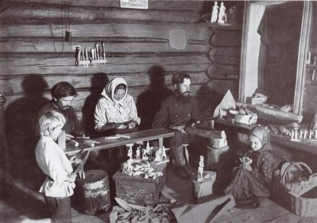 Семья за изготовлением деревянных игрушек.