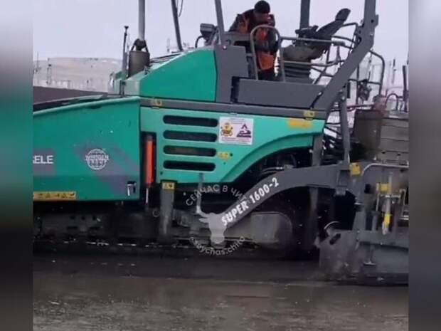 Дорожники на улице Трактовой в Чите укладывают асфальт в снег и лужи