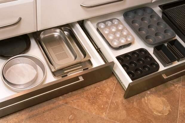 Выдвижные ящики в цоколе кухне помогут разместить много нужных вещей.