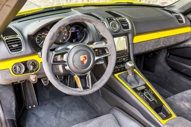 Передняя панель – как в обычном Бокстере. В коротком списке отличий – спортивный 360‑миллиметровый в диаметре руль без кнопок, укороченный рычаг безальтернативной механики да дверные матерчатые петли на месте привычных ручек.