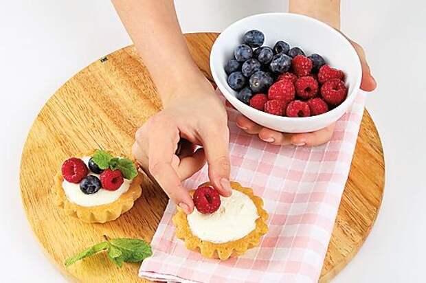 Остывшие корзиночки наполнить творожной массой и украсить ягодами.