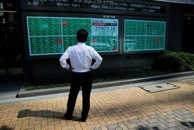 FILE PHOTO: A man watches an electric board showing Nikkei index outside a brokerage at a business district in Tokyo, Japan, June 21, 2021. REUTERS/Kim Kyung-Hoon/Files