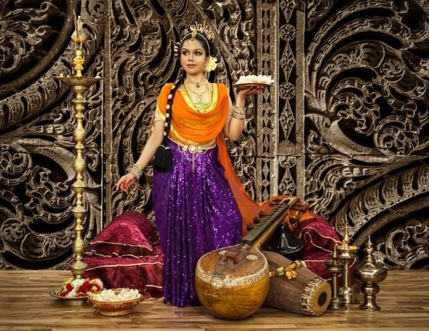 Девушка в индийском национальном костюме с блюдом сладостей в руке
