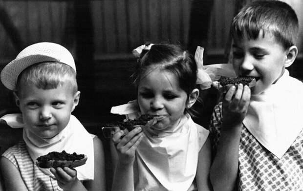 Трое детей наслаждаются бутербродами с икрой в детском саду. Июль. Москва,1965.
