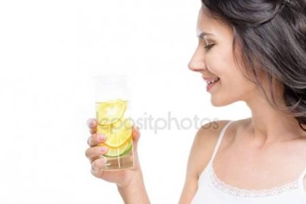 Женщина, держащая стакан воды с лимоном Стоковое Изображение