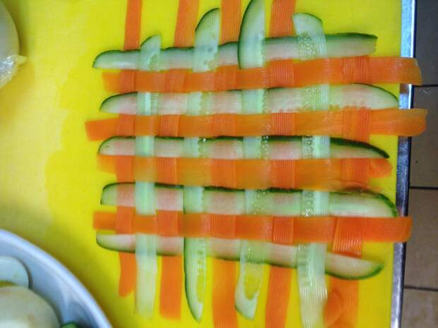 Морковные и огуречные полоски переплести в шахматном порядке, образуя простую плетенку