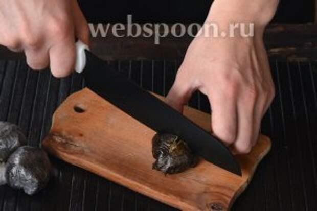 Развернуть целлофан и выложить суши на доску швом вниз. Острым ножом сделать сверху крестообразный надрез.