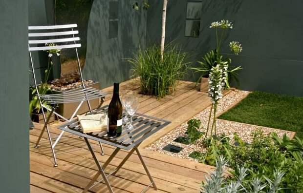 Хороший и нескучный вариант создать зону комфорта на веранде в окружении гармоничной садовой композиции.