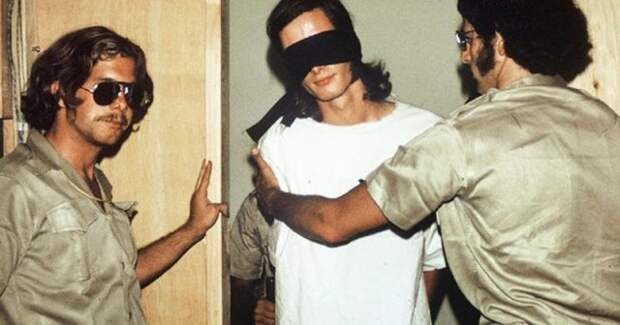 тюремные охранники и заключенный с завязанными глазами