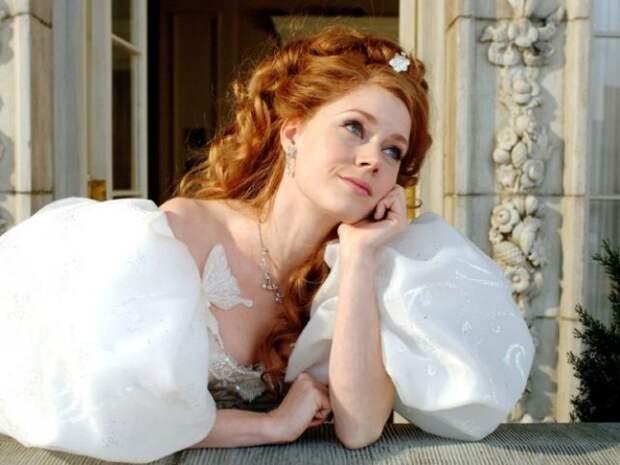 рыжая женщина в белом платье смотрит из окна