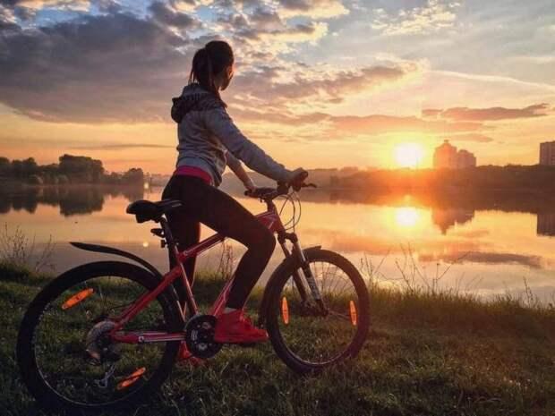 девушка на велосипеде смотрит на закат