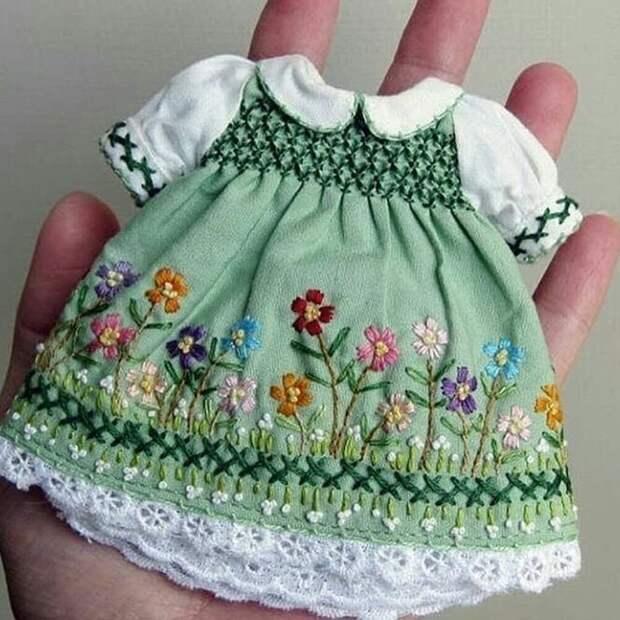 Девочка пошила крохотное платьице своей кукле.