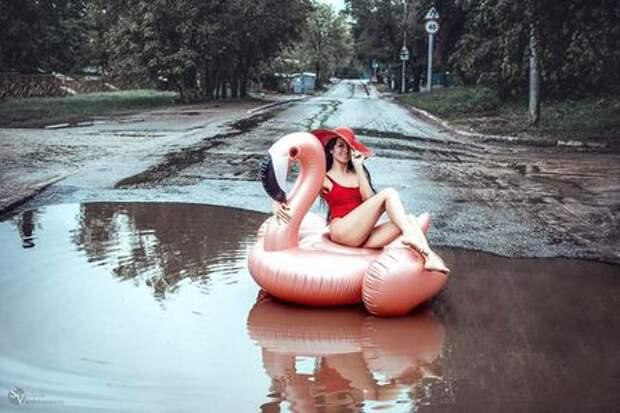 Девушка в купальнике добровольно села в лужу на дороге