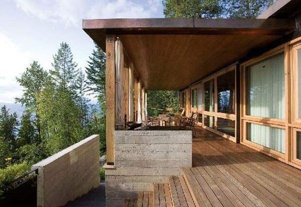Часть деревянного дома с шикарной террасой, с которой открывается вид на горы, озеро и окружающий лес.