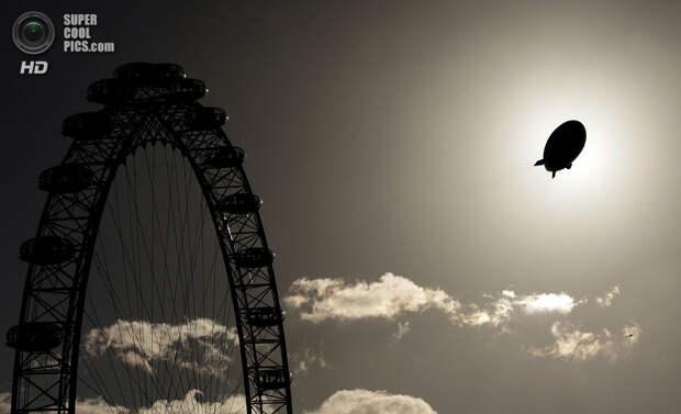 Великобритания. Лондон. 9 ноября 2006 года. Дирижабль, рекламирующий курорт в Дубаи, проплывает мимо Лондонского глаза. (Peter Macdiarmid/Getty Images)