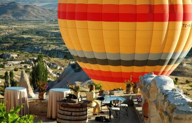 Женщина сидит на веранде Museum Hotel, пока воздушный шар взмывает в небеса