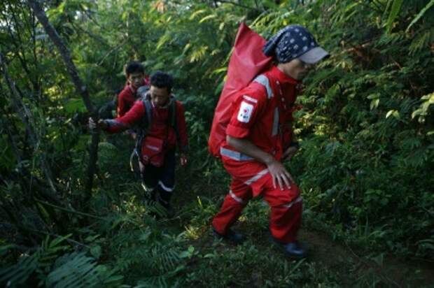 Tough terrain: Volunteers from the Indonesian Red Cross enter the climbing track in Cipelang, Cijeruk in the area of the Halimun Salak National Park in West Java to locate the exact crash location of the Sukhoi Superjet 100 on Friday. More than 200 joint personnel from the Indonesian military and police as well as the National Search and Rescue Agency (Basarnas) continued the evacuation process of the victims. (JP/Jerry Adiguna)