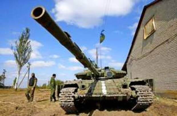 Ukrainian soldiers stand next to a tank near Donetsk