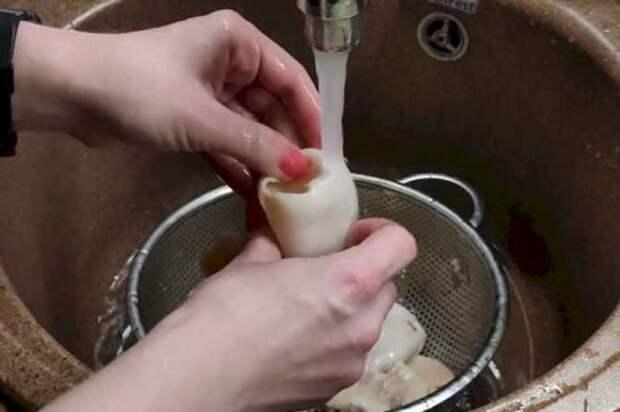 Промываем кальмары под холодной проточной водой. Параллельно очищаем от пленок и посторонних частей внутри.