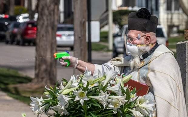 Американский священник окропляет прихожан святой водой из пистолета