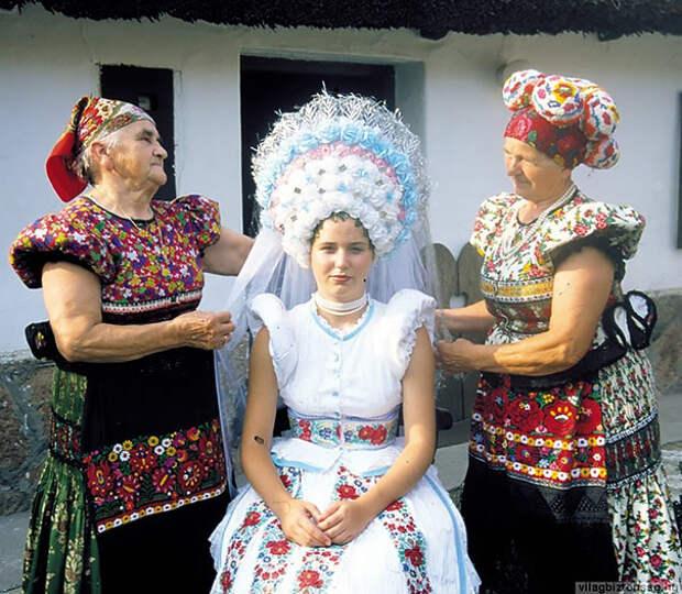 Свадебное платье состоит из цветочных узоров, которые выполнены из трех ярких цветов, а в головной убор вплетаются колоски пшеницы.