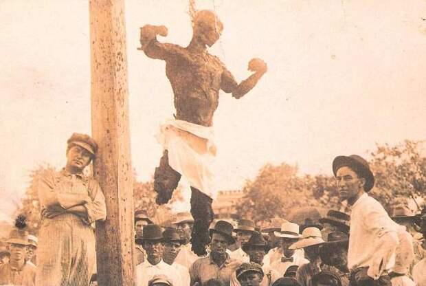Техасский парень, позирующий на фоне убитого Джесса Вашингтона. Техас, США, 1916 | Фото: glavpost.com