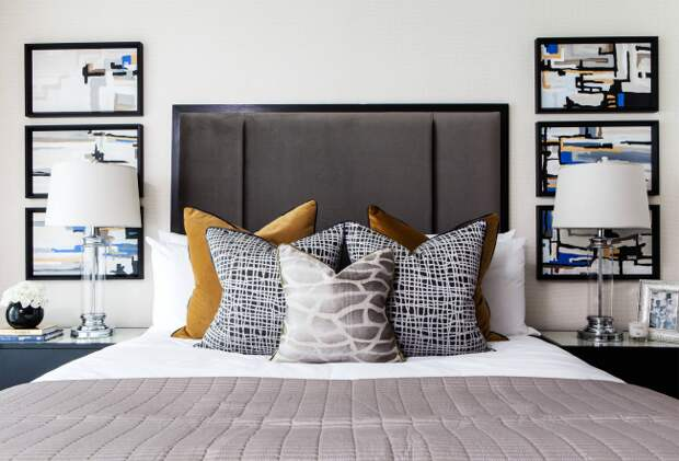 Оригинальные графические мотивы на обшивках подушек в светлой спальне