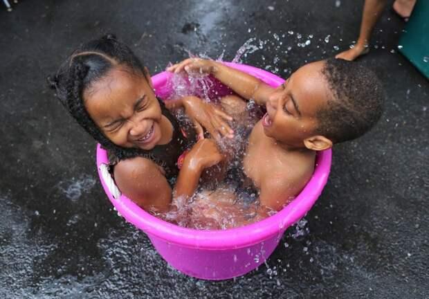 Дети купаются в ведре с водой