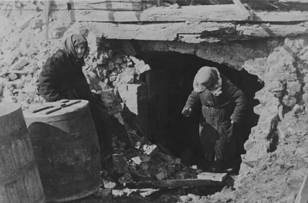 Две пожилые жительницы у входа в подвал разрушенного дома.