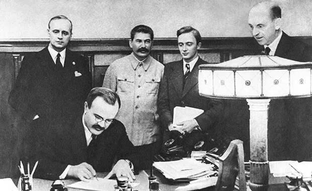 Вячеслав Молотов подписывает германо-советский договор о дружбе и границе между СССР и Германией. Стоят (слева направо) Иоахим фон-Риббентроп, И.В.Сталин, В.Н. Павлов, Ф.Гаус. ТАСС
