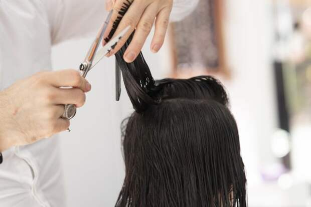 парикмахер стрижет девушку брюнетку