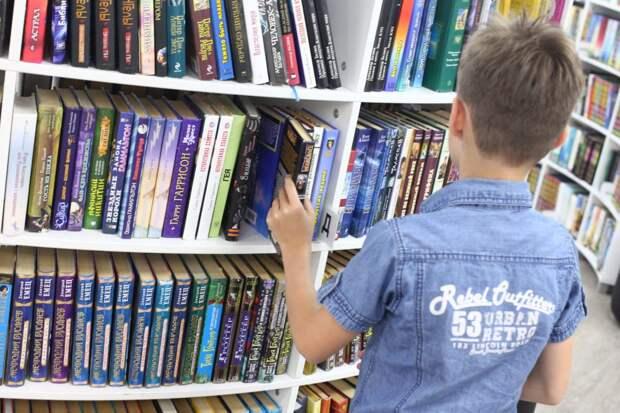 Школьник выбирает книги в библиотеке / Фото: Агентство Москва