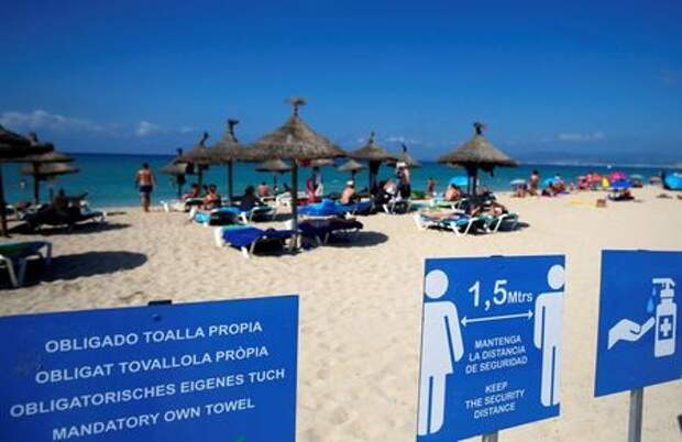 Signs are pictured as people sunbathe and swim on El Arenal beach, amid the outbreak of the coronavirus disease (COVID-19), in Palma de Mallorca, Spain August 15, 2020. REUTERS/Enrique Calvo