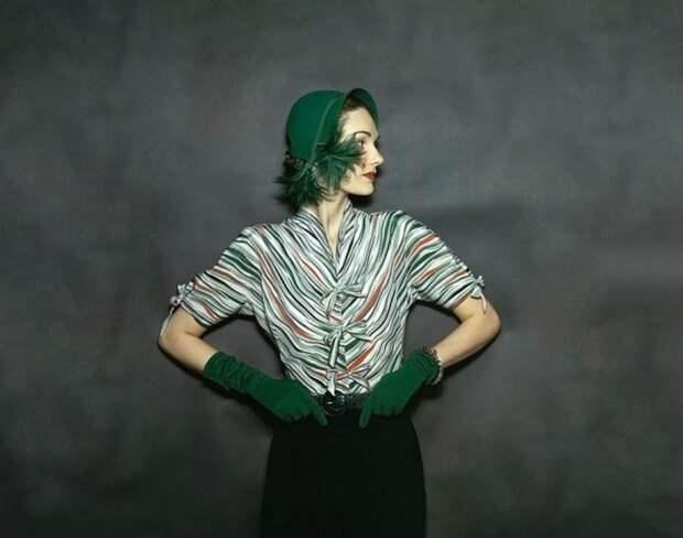 Модель в шерстяной юбке подпоясанной ремнем из змеиной кожи, шелковой полосатой блузе, шляпке и перчатках из тонкой шерсти в журнале Vogue 1944 года.