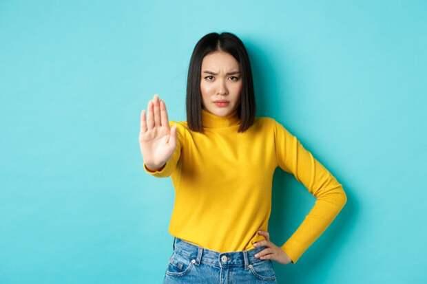 девушка выставила руку вперед в знак отказа