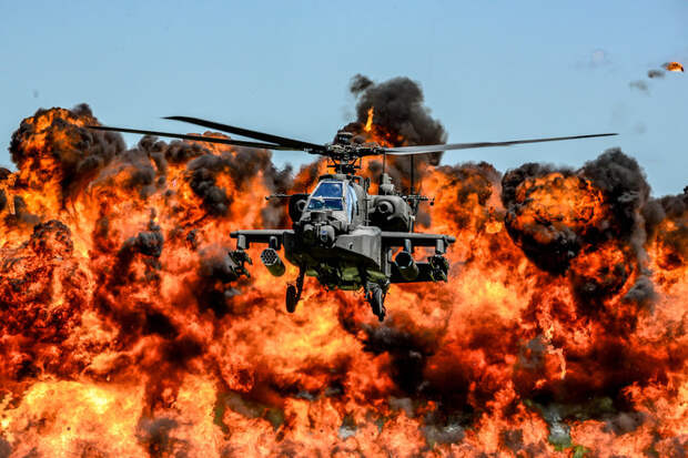 A U.S. Army AH-64D Apache Attack Helicopter, assigned to the 1-151st Attack Reconnaissance Battalion, flies in front of a wall of fire during the South Carolina National Guard Air and Ground Expo at McEntire Joint National Guard Base, South Carolina, May 6, 2017.