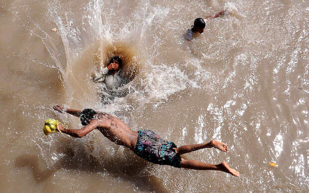 1) Пакистанские подростки плавают в арыке во время сильной жары в Лахоре 28 июня. (Arif Ali/AFP/Getty Images)