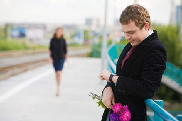 мужчина с букетом ждет женщину