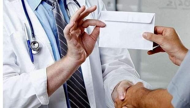 врач берет конверт со взяткой