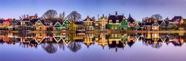 Дома стоят на берегу реки в Заансе Сханс, Нидерланды.Фотограф: Ханс Альтенкирх