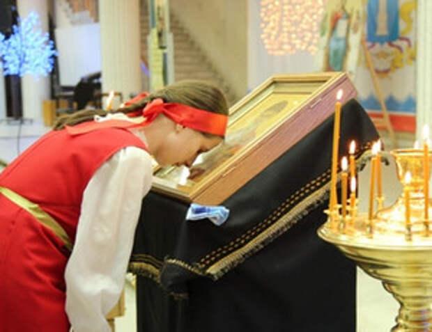 Девушка молится перед иконой