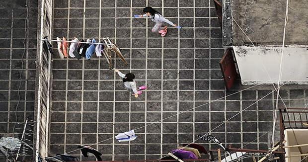 Француз подглядывает зажителями Гонконга накрышах небоскребов