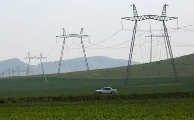 A car drives along a regional highway near electricity pylons, located in agrarian fields, in the Republic of Khakassia, Russia July 12, 2018. Picture taken July 12, 2018. REUTERS/Ilya Naymushin