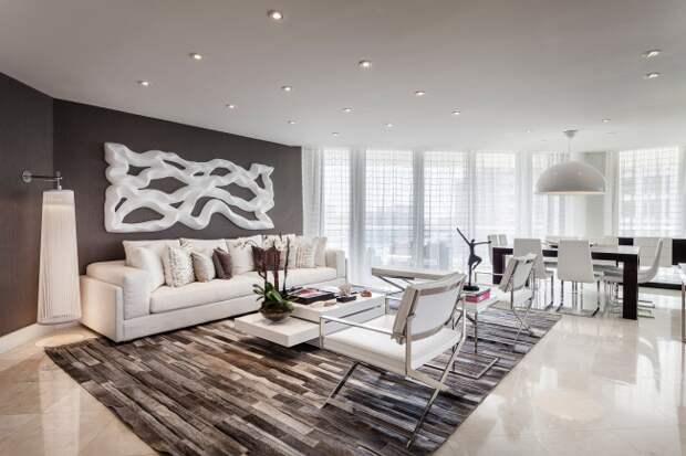 Большое студийное помещение просторной квартиры в серых тонах. Центр внимания - большая обьемная абстракция на стене над диваном, которая поддерживает общее настроение комнаты