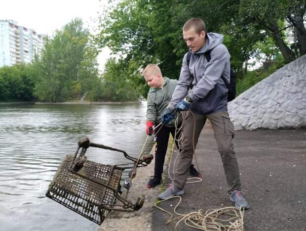 Денис Щелкушин с младшим братом вытаскивают из воды тележку/Из личного архива