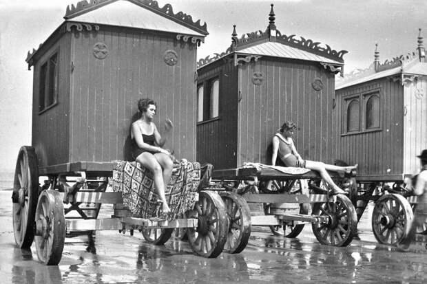 Девушки загорают в купальных машинах.